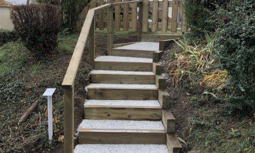 Escalier en pin traité, main courante et clôture sur mesure avec portillon d'accès piéton